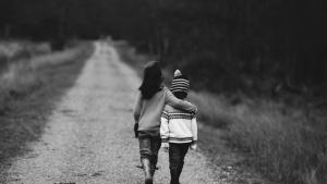 Black and white photo of two children walking down a road, each with an arm around the other's shoulders.
