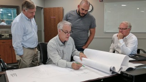 Peter Eddington and Rudy Rangel look at the new addition plans with Mark Bredemeier and Mike Barnard.