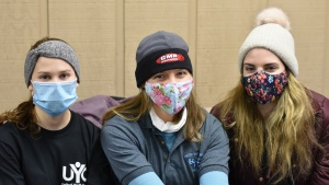 Three ladies on nursing staff at winter camp smile with masks on.