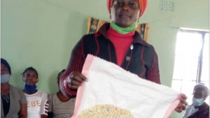 Lucia Mulenga holds up a nearly finished doormat.