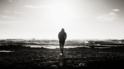 A main walking by the ocean shoreline.