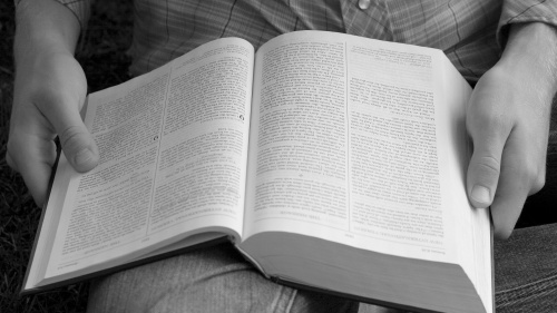A person holding a Bible on their lap.