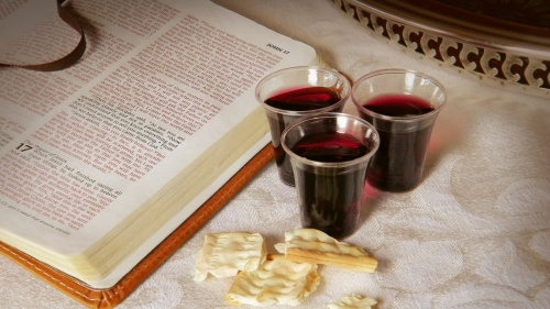 An open Bible with small cup of wine and unleavened bread.