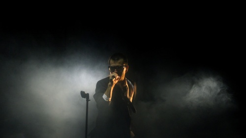 A man singing into a microphone on dark foggy stage.