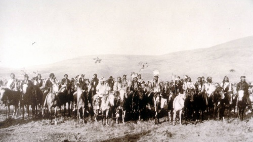 A large group of men on horseback with mountains in the background. In the front center of the group can be seen Chief Joseph, White Bird and Looking Glass.