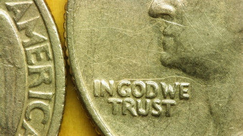 "Close up of United States quarter displaying the phrase ""In God We Trust""."