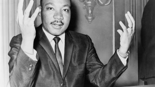 Rev. Martin Luther King, head-and-shoulders portrait, seated, facing front, hands extended upward, during a press conference.