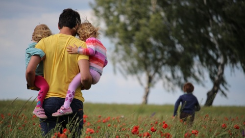 A father walking in field carrying two daughters.