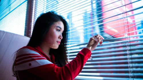 A young woman looking out a window.