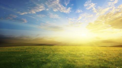 Sunrise of over a green grass hill