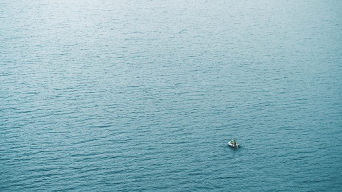 A tiny boat in a big sea of water.