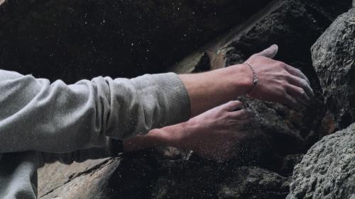 A rock climber's hands gripping onto rock cliff.