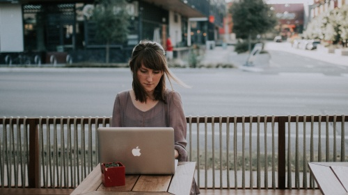 A young woman looking a laptop screen.