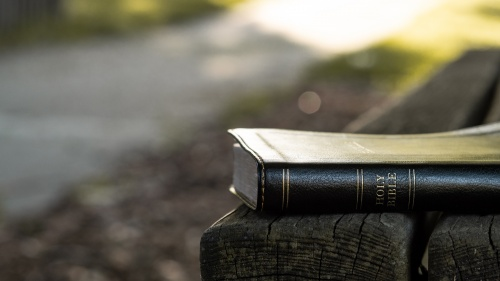A Bible laying on a park bench.