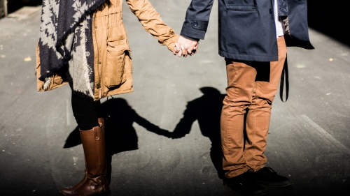 A young couple holding hands while walking.