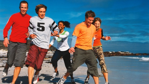 Young adults running on the beach.