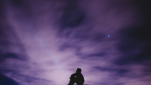 A man sitting looking at the stars.