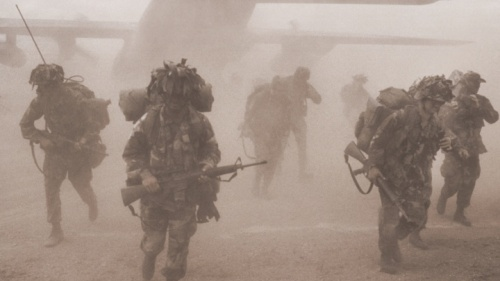 Soldiers coming out of an airplane.