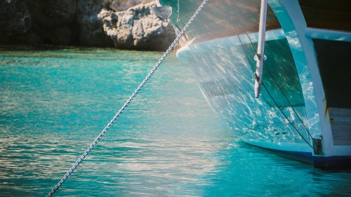 A boat in the water with a chain going down into the water attached to an anchor.