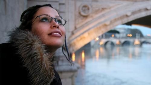 A woman standing beside an old bridge.