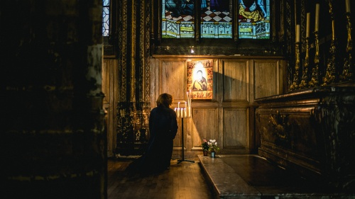 A woman praying to a painting hanging in a church.