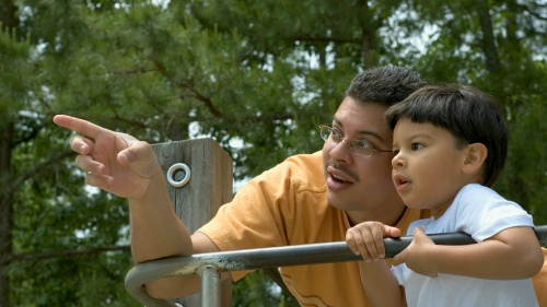 A dad and son playing at a park.