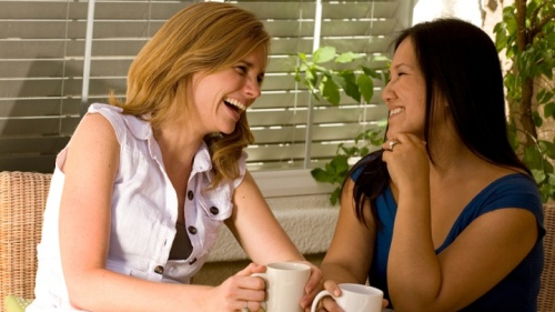 Two women laughing and talking together.