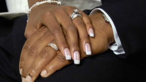 A couple holding hands showing their wedding rings.