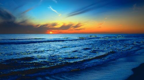 Blue and orange sunrise over an ocean.