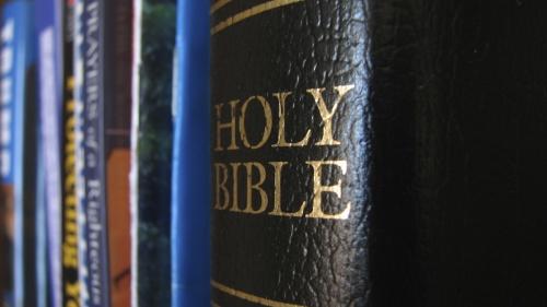 Bible on a book shelf.
