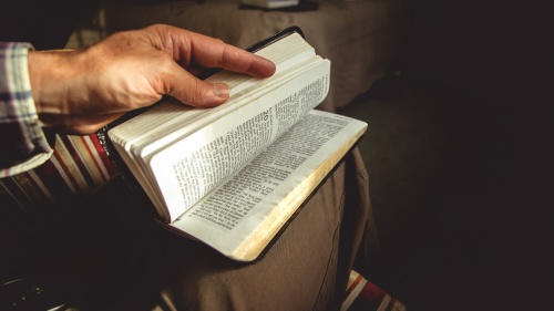 A man holding a Bible on its lap flipping through pages.