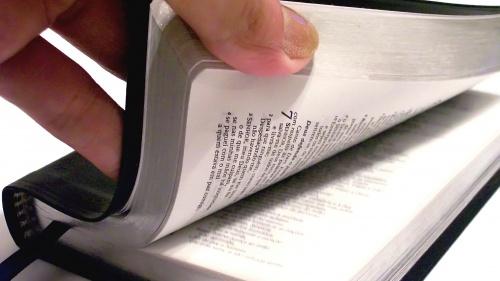A person's hand thumbing through a Bible.
