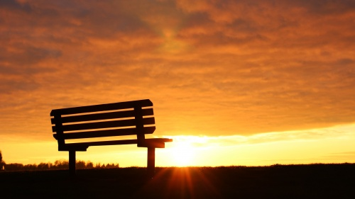 A empty bench with the sun setting.