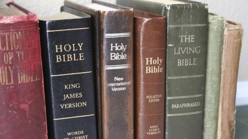 Various Bibles on a shelf.