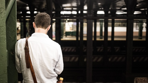 A man waiting at a subway station.