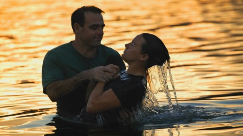 A scene of a person getting fully submersed in a water baptism.
