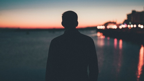 A silhouette of young man looking out over a body of water.