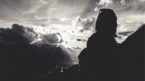 Woman with sun rays in background.