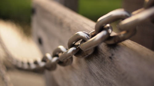 Heavy chain across a piece of wood.