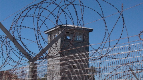 Barbed wire fence and tower in a prison yard.