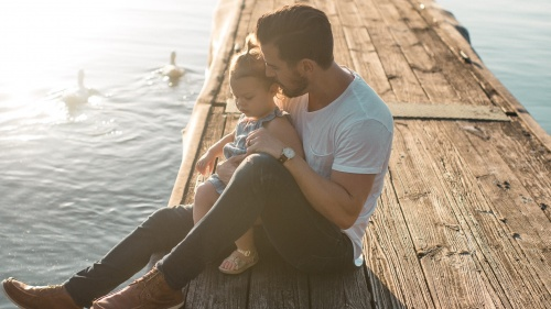 A dad sitting with his daughter.