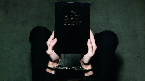 A person holding a Bible while their hands are wearing shackles.