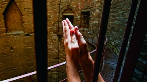 Praying hands reaching through the bars of a prison.