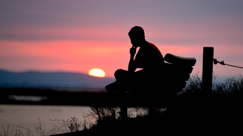 A person sitting on bench while the sun is setting.