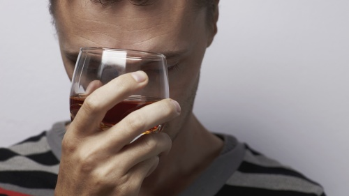 A person holding a glass of alcohol.