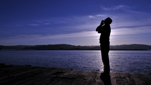 A person looking up to the sky and praying.