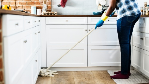 A person cleaning a kitchen floor with a mop.