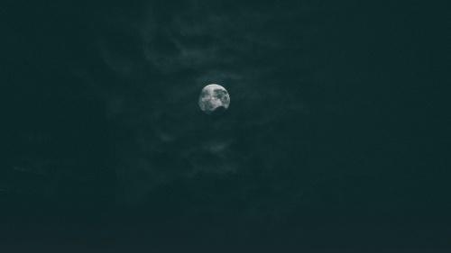 The moon through dark clouds.