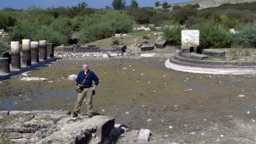 Scott Ashley standing at the edge of the harbor at Miletus, with the silted-in harbor and the remains of the monument behind him at the right.