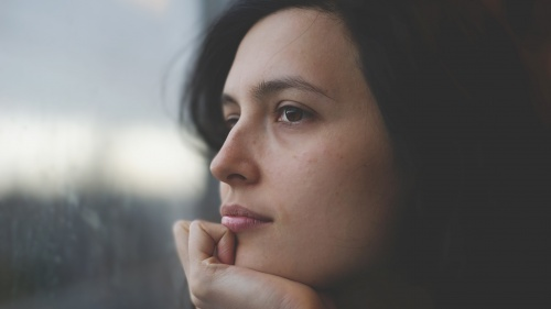An upclose photo of woman's face looking out a window.
